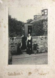 Black and white photograph taken by John Spark of Perth showingAnna Geddes, Miss Scott, Janet Cuthbertson, Norah and Alasdair Geddes at the garden gate of Mount Tabor cottage, Perth, c.1899