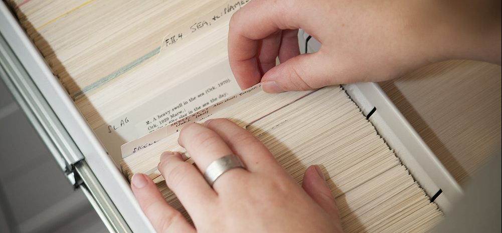 Hands search through a card index