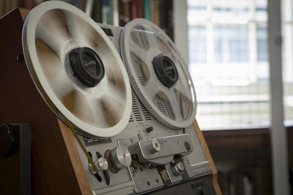 colour photograph of a reel to reel machine in action. The focus over the reels is blurred to show the fast movement