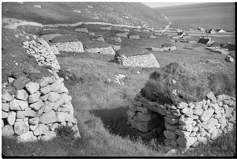 a black and white image of St Kilda, there are many stone built cleits with turf roofs.
