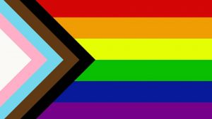 An image of progress pride. It Includes the rainbow flag design, with arrows to the left of the trans flag and representation of people of colour in pride and the community.