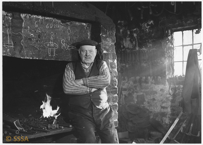Black and white image of a blacksmith who is sitting on the edge of a fireplace, a flame behind him. TThere are chalk drawings on the breast of the chimney. Light is streaming in a window just out of shot