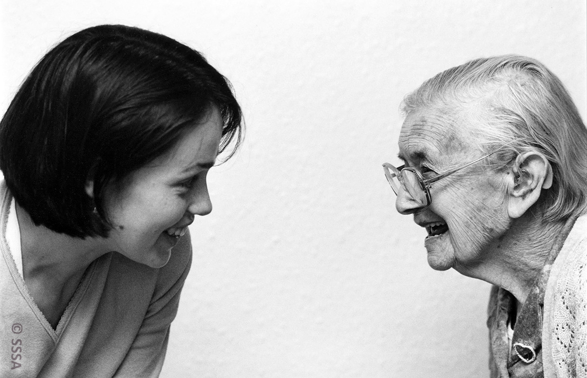 Black and white image of two women in side profile, Dr K Campbell looks at her interviewee Lizzie Angus. They smile openly towards eachother