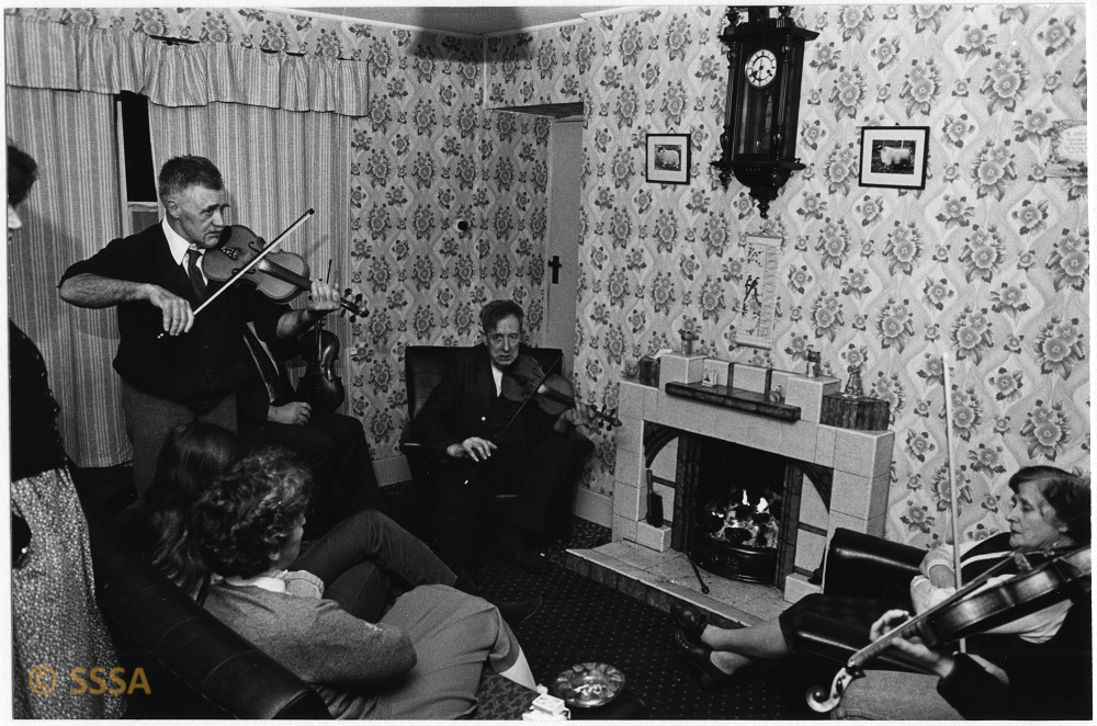 black and white image of a group of people in a sitting roo,. a man stands with a fiddle , two others are seated with fiddles.