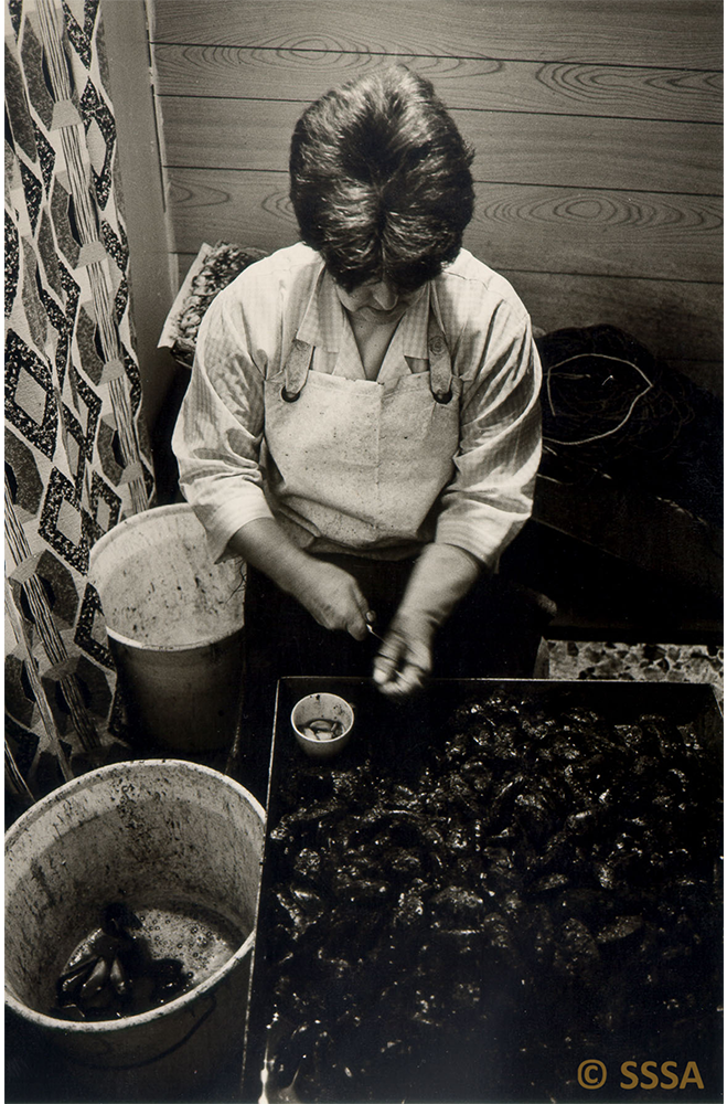 black and white image of a woman, head down, bust at work baiting lines
